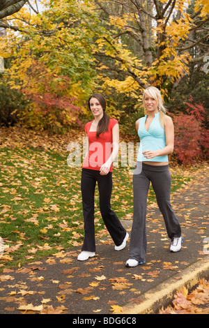 Portrait of two young women walking in fitness attire - Stock Image