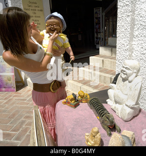 Mother holding Buddha mask in front of toddler's face while shopping for craft items, Mijas Pueblo, Costa del - Stock Image