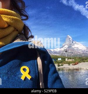 Catalan tourist with a yellow ribbon pinned in her blue jacked  in support of jailed pro-independence Catalan politicians . View of Matterhorn, Zermatt, Wallis or Valais, Switzerland - Stock Image