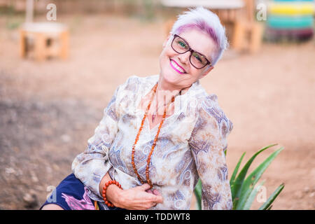 Beautiful alternative senior mature woman with punk hipster hippy style white and violet hair smile at the camera posing for a portrait - happiness an - Stock Image