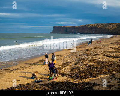 Families walking on Saltburn Beach on an unseasonably warm February day in spring sunshine blue sky and a view south towards Huntcliff - Stock Image