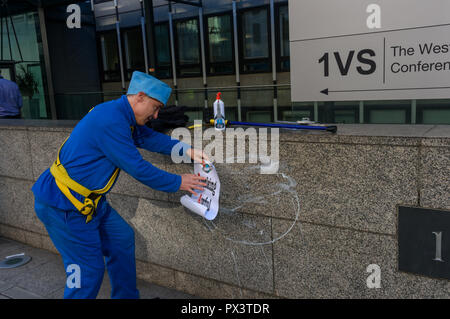 London, UK. October 19th, 2018. 'Commander Neil Godwin Tracy' of International Rescue begins to put a poster on the wall of  the Dept for Business, Energy and Industrial Strategy (BEIS) after he had been refused entry. He had come to offer his organisation's assistance, to produce policies which which recognise the desperate need to cut carbon emissions to avoid disastrous global warming and climate change by banning all fracking. Security staff at the ministry, which campaigners allege has spent more time on changing its name than developing sensible policies, refused to allow him to enter or - Stock Image