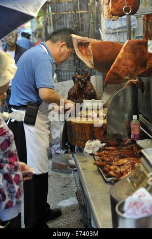 Man cutting pork chops in sidewalk butcher's shop, Kowloon, Hong Kong, China - Stock Image