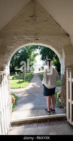 Lady Standing in church doorway UK - Stock Image
