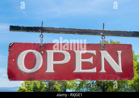 Open business old red and white vintage sign hanging from black metal pole - Stock Image
