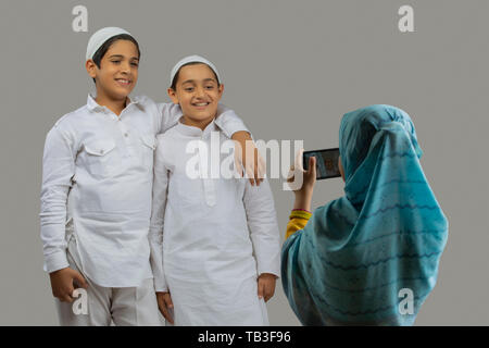 young Muslim girl clicking picture of young Muslim boys - Stock Image