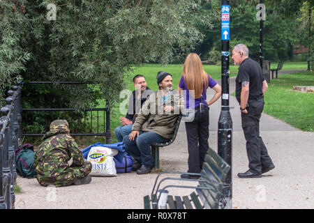 A  town host chatting to a group of men with personal belongings around their feet, (possibly homeless) next to the river Avon in Chippenham - Stock Image