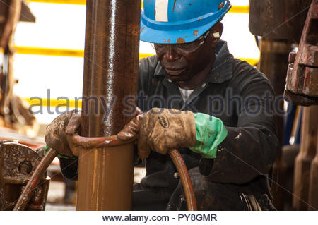 Worker holding hose on dirty pipe - Stock Image