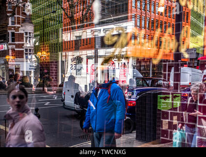 multiple reflections of a busy city in shop window. - Stock Image