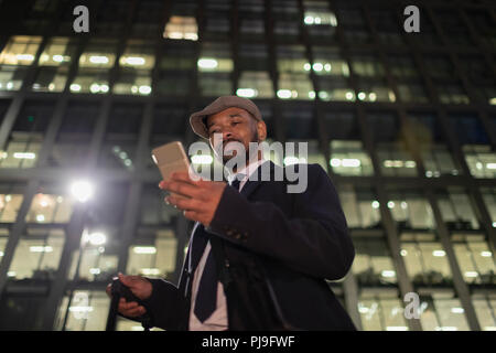 Businessman with smart phone standing below urban highrise at night - Stock Image