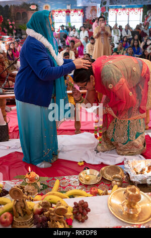 A devout Hindu woman celebrates her 70th birthday bu assisting in the services at a temple in Jamaica, Queens, New York City. - Stock Image
