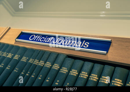 Official Journals sign above shelf full of books in library - Stock Image