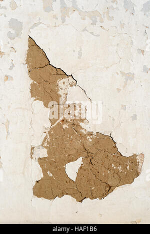 Cracked white plaster all with flaking plastering. Copyspace area for DIY and home improvement repair designs and - Stock Image