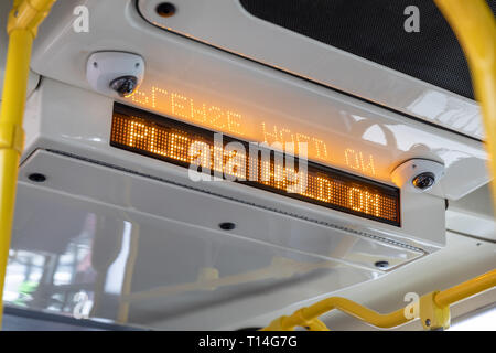 'Please Hold On' LED sign in bus - Stock Image