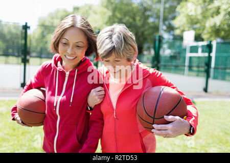 Active senior women friends playing basketball in sunny park - Stock Image