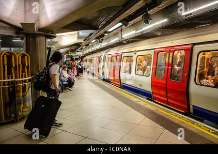 A train arrives at Westminster London Underground Station as passengers wait on the platform. - Stock Image