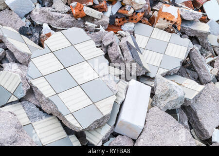Building debris heap from broken tiles, bricks and concrete. Construction waste pieces close-up. Damaged old floor and masonry. Demolition, earthquake. - Stock Image