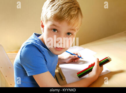 Cute left handed boy, drawing with colored pencils - Stock Image