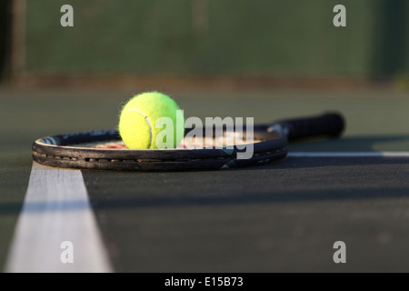 Tennis racket, ball laying on court. - Stock Image