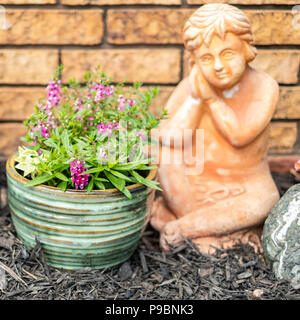 A stone garden cherub next to a pot of pink Angelonia flowers by a brick wall. USA - Stock Image