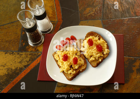 Scrambled egg on toast with plum tomatoes. Background is a tiled table top and shows salt and pepper mills - Stock Image