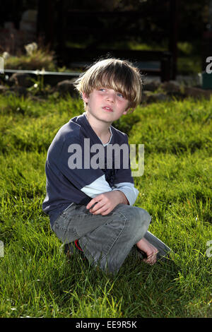 A young blonde haired boy sits in a sunny garden and is lost in thought - Stock Image