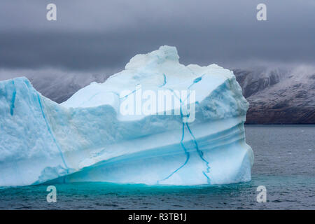 Greenland. Northeast Greenland National Park. Kong Oscar Fjord. Iceberg shows veins of frozen meltwater. - Stock Image