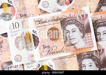Ten pound notes, England. UK currency cash money GBP bank note with a penny coin 1p. - Stock Image