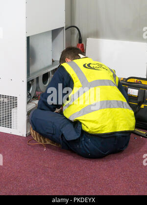 Electrical Technician making an on-site repair to a air conditioning unit in a commercial premises - Stock Image
