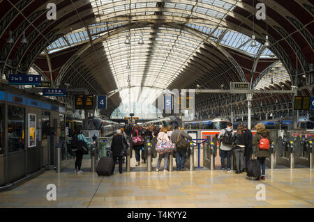 Travellers go through the turnstiles to their trains at Paddington Station, London - Stock Image