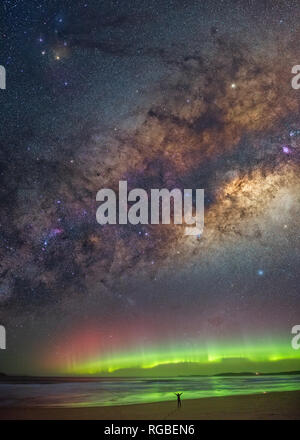 Lone figure in silhouette, standing in amazement with arms outstretched under the aurora and Milky Way - Stock Image