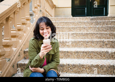 Happy young woman in green jacket using her smart phone sitting on stairs outdoors - Stock Image