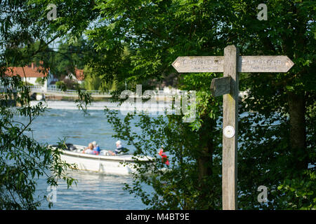 A wooden Thames Path sign marking the public footpath running alongside the river Thames with a small boat. England - Stock Image