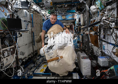 Canadian Space Agency astronaut David Saint-Jacques moves a U.S spacesuit inside the Destiny laboratory module March 19, 2019 in Earth Orbit. - Stock Image