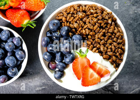 Chocolate Flavoured Breakfast Cereals With Fresh Fruit, Coco Pops, Strawberries, Blueberries and Yogurt. - Stock Image