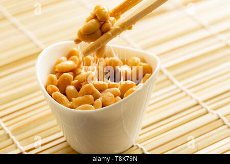 Eating healthy traditional japanese fermented soybeans called natto with chopsticks - Stock Image