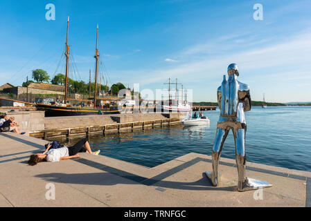 Oslo Norway summer, view of a woman sunbathing beside a sculpture of a silver diver (Dykkar) on a quay in the harbour area (Aker Brygge) of Oslo. - Stock Image