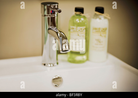 Toiletries on a bathroom sink - Stock Image