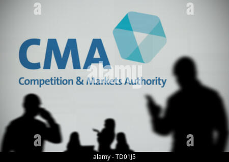The CMA logo is seen on an LED screen in the background while a silhouetted person uses a smartphone in the foreground (Editorial use only) - Stock Image