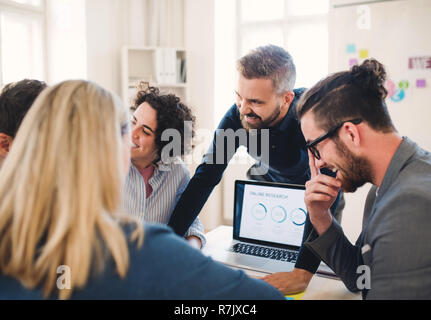 Group of young, cheerful, male and female businesspeople with laptop working together in a modern office. - Stock Image
