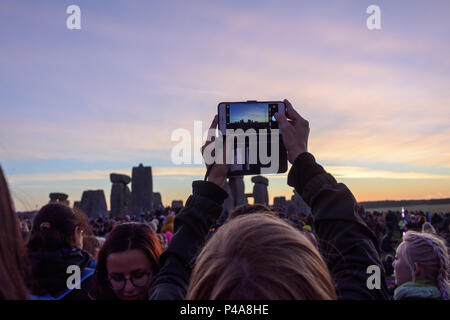Stonehenge, Amesbury, UK, 21st  June 2018,   Taking pictures of the sunrise on a moble phone at the summer solstice  Credit: Estelle Bowden/Alamy Live News. - Stock Image