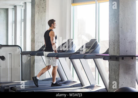 Side view of young adult sport man training at gym alone. Handsome male walking on treadmill and looking to window. Indoor, healthy fitness concept, a - Stock Image