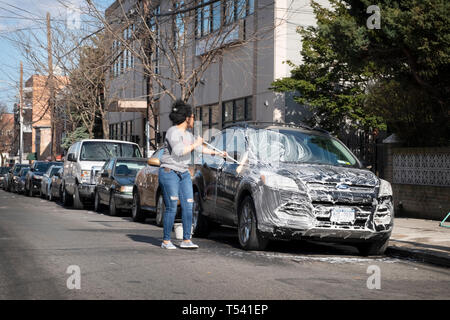 A woman washing her SUV with soap and water on a side street in Corona, Queens, New York City - Stock Image