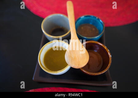 four colorful bowls with sauces and wooden spoon in brown ceramic tray with on black table with red straw place mats - Stock Image