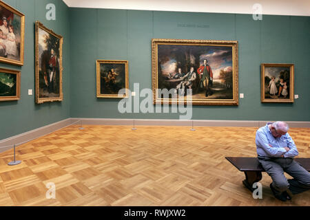Visitor sleeping in a bench in the Drub Heinz gallery, The Metropolitan Museum of Art, Manhattan, New York USA - Stock Image