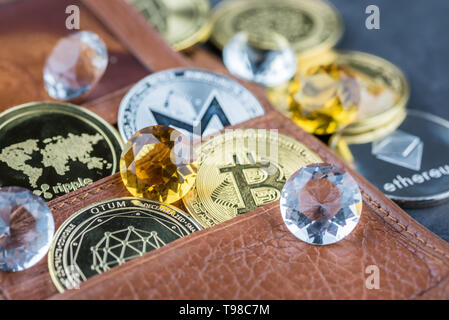 View of different kind of metal bitcoins in brown leather wallet and diamonds.Concept image for cryptocurrency - Stock Image