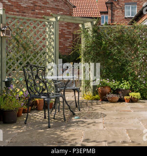 Small domestic garden patio with metal table and chairs, natural stone slabs and painted trellis - Stock Image