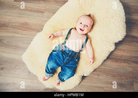 Little boy at home. Adorable baby resting on the fur blanket on the wooden foor. - Stock Image