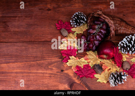 Thanksgiving decor with horn of plenty, frosted pine cones, apple, grapes and maple leaves - Stock Image