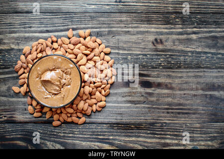 Whole fresh almonds with a bowl of freshly ground creamy almond butter over a rustic table or background. - Stock Image